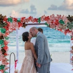 Colorful paper flowers adorn their beachside ceremony arch | Whyman Photography