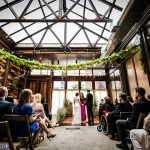 Airy Atrium Ceremony at Brooklyn Winery hung with Garlands of Greenery | Kelly Williams, Photographer | https://heyweddinglady.com/romantic-rustic-urban-wedding-at-brooklyn-winery/