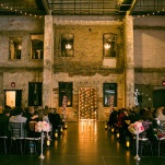 Industrial Ceremony Site with Gleaming Lights and Pink Flowers | Erin Johnson Photography | See More! https://heyweddinglady.com/romantic-industrial-glam-wedding-from-erin-johnson-photography/