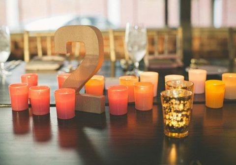 Vibrant Orange Votive Candles with Gold Table Numbers | Jason Hales Photography | See More! https://heyweddinglady.com/modern-art-nouveau-wedding-inspiration-glittering-gold-orange-blue/