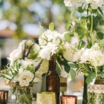Fresh White and Green Centerpieces in Vintage Bottles and Jars | Vitaly M Photography | See More! https://heyweddinglady.com/historic-villa-wedding-in-southern-california/