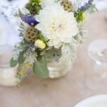 Rustic Cream and Purple Centerpieces on a Burlap Runner | Dawn Heumann Photography | See More! https://heyweddinglady.com/romantic-bespoke-wedding-handmade-by-friends/