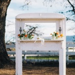 A Vintage White Mantelpiece with Orange Flowers for a Romantic Ranch Wedding Ceremony Backdrop | Lisa Mallory Photography | See More! https://heyweddinglady.com/autumn-harvest-wedding-at-santa-margarita-ranch/