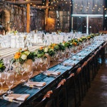 Guests Sat at Vintage Farm Tables with Burlap Runners in the Barn under Bistro Lights | Lisa Mallory Photography | See More! https://heyweddinglady.com/autumn-harvest-wedding-at-santa-margarita-ranch/