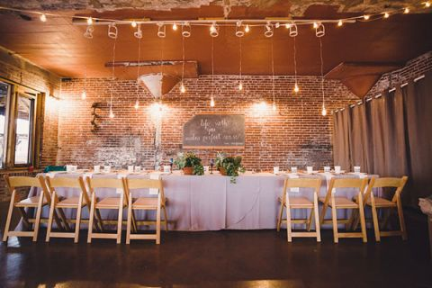 Modern Industrial Wedding Reception With Exposed Brick And Hanging Edison Light Bulbs