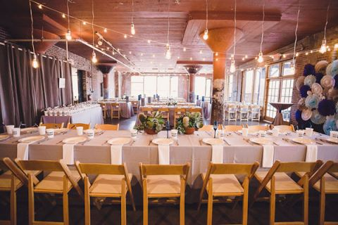 Hanging Edison Lights, Exposed Brick, and a Paper Pinwheel Backdrop for a Modern Chic Wedding Reception | Oldani Photography | See More! http://heyweddinglady.com/modern-chic-blue-white-and-silver-wedding