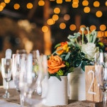 White and Orange Centerpieces with Table Numbers in Reclaimed Wood | Lisa Mallory Photography | See More! https://heyweddinglady.com/autumn-harvest-wedding-at-santa-margarita-ranch/