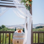 Fluttering Drapery and Floral Ceremony Brackdrop | Lisa Mallory Photography | Modern Ranch Wedding in Orange and Aqua
