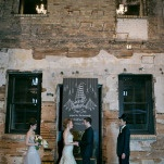 Exposed Brick and Chalkboard Ceremony Backdrop | Erin Johnson Photography | Iron and Velvet Romantic Steampunk Wedding
