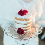 Bride Holding a Petite Naked Cake adorned with Red Rosebuds | Samantha Kirk Photography | Red Velvet - Luxe Winter Styling in Leather and Lace