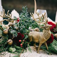 Sleigh Bells and Bronze Deer in a Greenery Runner | Nicole Colwell Photography | https://heyweddinglady.com/festive-styled-wedding-in-the-winter-woods-with-a-corgi-in-a-holiday-sweater/