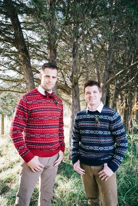 Groom and Groomsman in Navy and Red Sweaters   Nicole Colwell Photography   https://heyweddinglady.com/festive-styled-wedding-in-the-winter-woods-with-a-corgi-in-a-holiday-sweater/