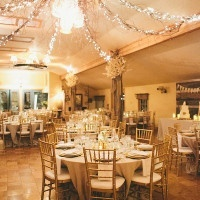 Wedding Reception Under Glowing Rustic Chandeliers | onelove photography | Classic Winter Elegance for a Rustic Vintage Barn Wedding