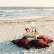 A Table for Two with Candles and Velvet Pillows | JoPhoto | Marsala and Champagne Engagement on the Beach - https://heyweddinglady.com/marsala-and-champagne-engagement-on-the-beach/