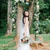Draped Floral Garland for a Garden Ceremony Backdrop | Rachel May Photography and Amore Events by Cody | Garnet and Rose Gold - An Enchanted Garden Wedding Editorial - https://heyweddinglady.com/garnet-and-rose-gold-an-enchanted-garden-wedding-editorial/