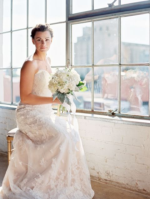 Elegant Lace Wedding Dress with a Fresh White and Green Bouquet