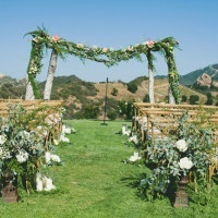 Elaborate Greenery Ceremony Arbor | onelove photography | Stylish Rockstar Wedding at a Southern California Vineyard in Ivory, Coral, and Gold