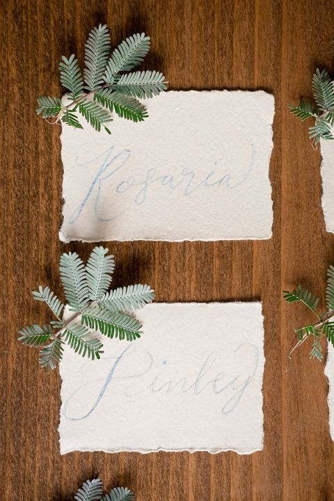 Calligraphy Escort Cards with Evergreens | Gavin Farrington Photography | Event Design and Styling by Glow Event Design - https://heyweddinglady.com/winter-chic-intimate-holiday-wedding-cozy-neutrals-2