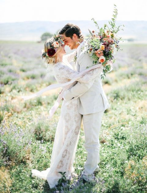 Whimsical Bohemian Bride and Groom with a Lace Wedding Dress in a Lavender Field | Tessa Barton Photography | https://heyweddinglady.com/wild-heart-carefree-bohemian-wedding-peach-sage/