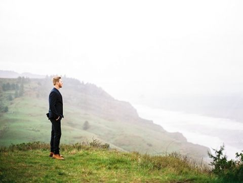 Groom Overlooking the Coast | Perry Vaile Fine Art Film Photography | https://heyweddinglady.com/moody-misty-beach-engagement-shoot/