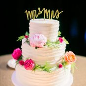 Ruffled Wedding Cake with Fresh Flowers and a Gold Calligraphy Cake Topper