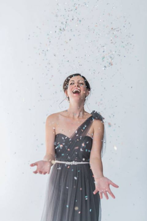 Bridesmaid in a One Shoulder Gray Dress Tossing Confetti