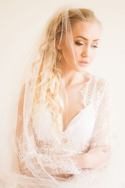 Bride in a Lace Robe and Veil Before the Wedding