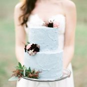 Bride Holding a Blush and Blue Cake
