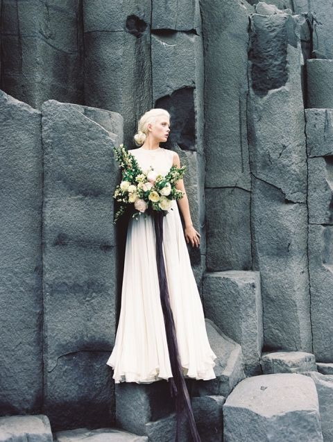 Ethereal Wedding Dress against a Rugged Rock Wall