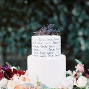 Love Letter Wedding Cake Surrounded by Jewel Tone Flowers