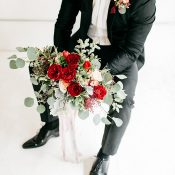 Groom in Black Tie with an Organic Red and Green Bouquet