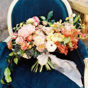 Bright and Colorful Summer Wedding Bouquet on a Blue Velvet Chair