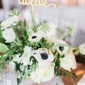 Gold Calligraphy Table Numbers in a Greenery Centerpiece