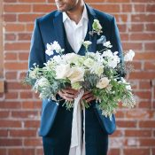 Groom Holding an Organic Floral Bouquet in Green and White