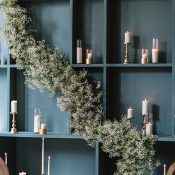 Glam Ceremony Backdrop with a White Baby's Breath Garland and Modern Candleholders