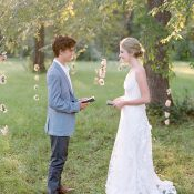 Exchanging Vows in a Sunlit Meadow with a Hanging Flower Backdrop