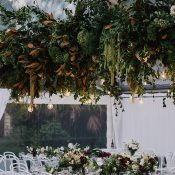 Modern Botanical Greenery and Edison Bulb Chandelier for a Marquee Reception