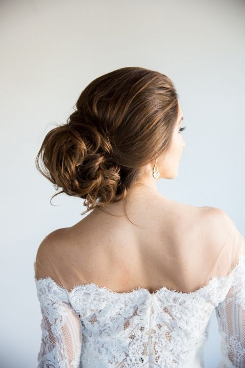 Romantic Messy Updo Bridal Hairstyle with a Loose Bun and Off the Shoulder Wedding Dress
