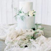 White and Blue Wedding Cake with a Raw Silk Table Runner
