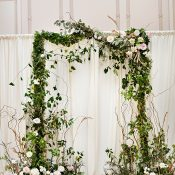 Indoor Garden Wedding with a Greenery and Floral Ceremony Arch