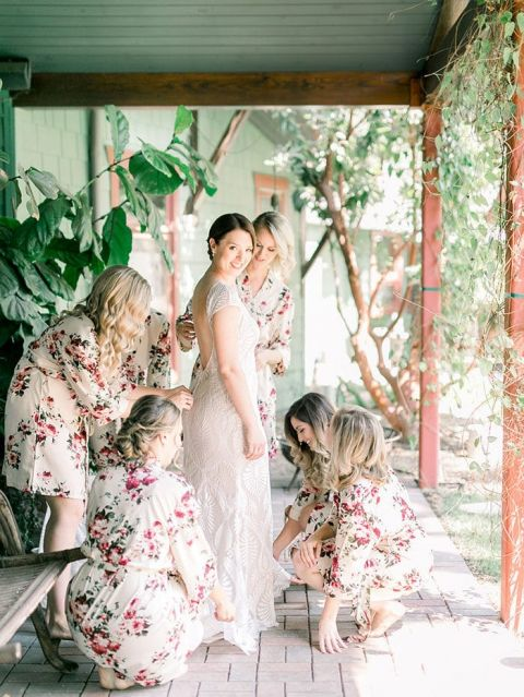 Bridesmaids Helping the Bride into her Wedding Dress
