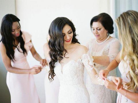 Bridesmaids Helping the Bride Put on her Wedding Dress