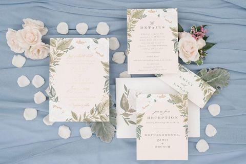 Floral wedding invitations on a dusty blue background