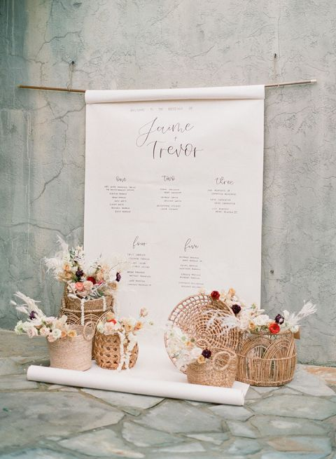 Woven Basket Centerpieces Accent a Hand Lettered Seating Chart Display