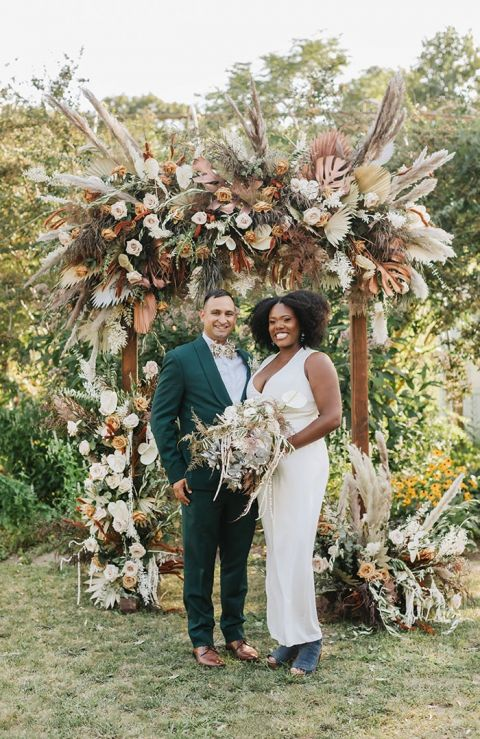 Savanna Inspired Flower and Dried Grass Wedding Ceremony Arch with a Stylish Bridal Jumpsuit