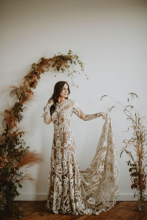 Indoor Fall Wedding Ceremony with a Foliage Arch and a Tattoo Lace Rue de Seine Dress