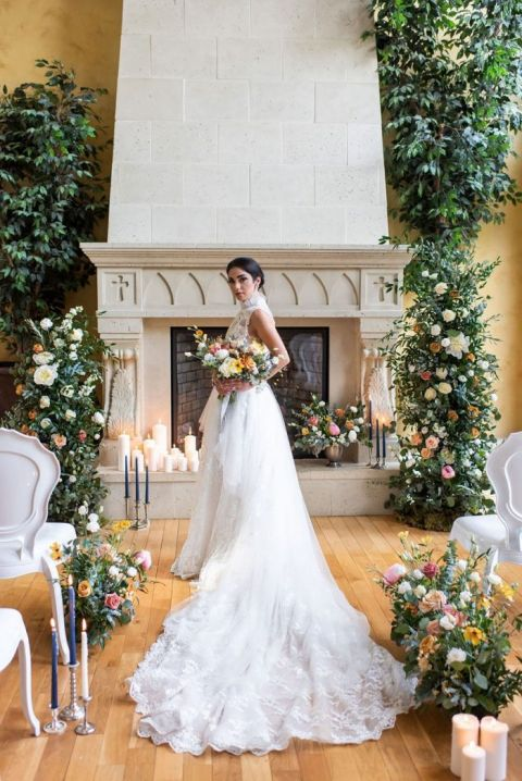 Cozy Indoor Castle Wedding Ceremony with Greenery and Candle Mantel Decor